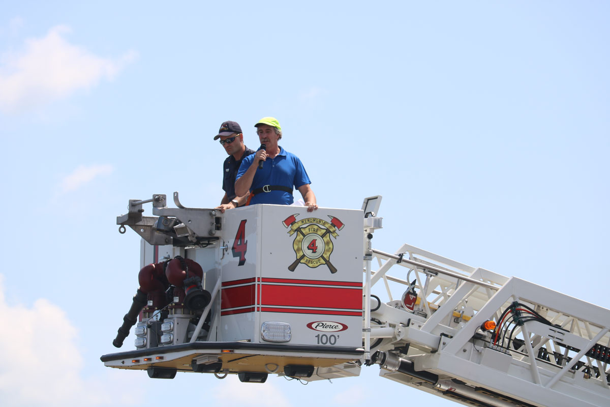 Mayor Randy Knaack singing national anthem from hook and ladder truck.
